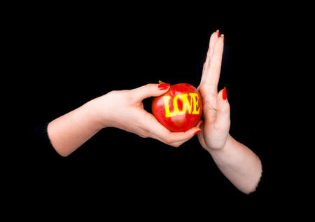 lesbian women: One female hand proposing an apple with a word LOVE and the other womans hand refusing it in a black background Stock Photo