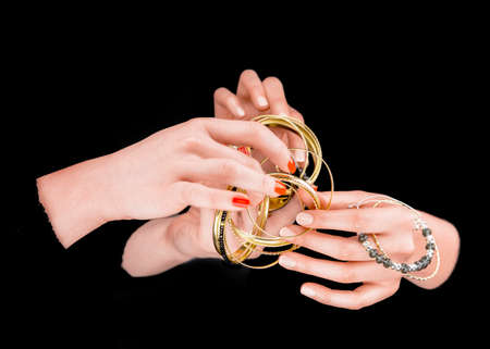 girl in love: Two womens hands with golden bracelets  in a black background