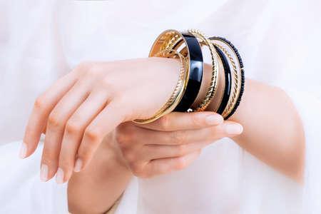 De handen van het meisje met gouden armbanden op een witte achtergrond