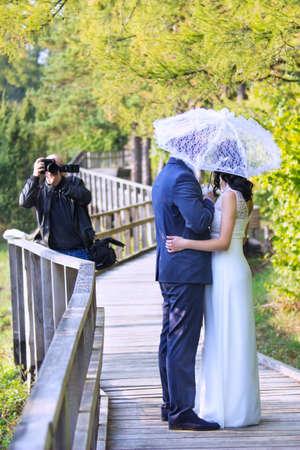 Huwelijksfotograaf die foto's van bruidegom en bruid met een witte paraplu in de zomer nemen