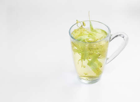 nontraditional: Cup of linden flower tea with blossoms inside on a white background