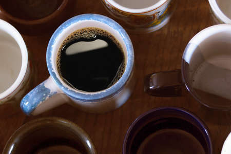 emty: Many various emty cups for tea or coffee on a wooden table. One of them with coffee