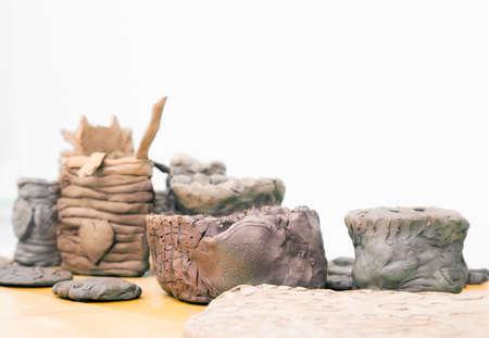 amateur: Muchos hechos a mano de aficionados molduras de arcilla sin cocer sobre una mesa de madera