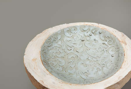 simulate: Unbaked decorative plate with ornament in a gypsum form on a grey background Stock Photo