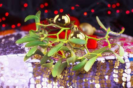 적합: Christmas decorations with mistletoes branches, golden toys and red blurry lights. Suitable for a postcard. 스톡 콘텐츠