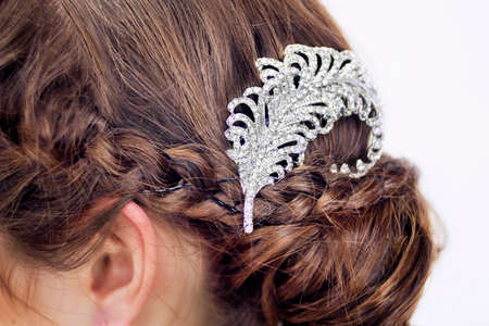 hairpin: Close view of a fancy diamond brooch in brunettes hair.