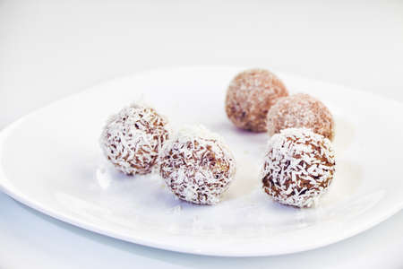 psyllium: Homemade raw dates truffles with nuts, psyllium and coconut flakes on a white plate and white background