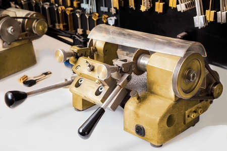 machinetool: Close view of key copying machine and blank keys on a wall . Stock Photo
