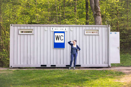 latrine: Woman keeping her nose with two fingers at a public toilet with sign WC in the city park in a summer time