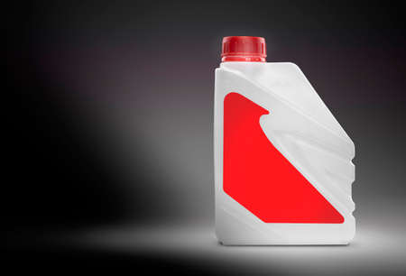 greasing: White plastic canister with blank red label on a black gradient background