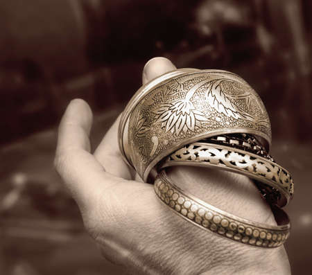 Feminine bracelets on a mans thumb in a white background