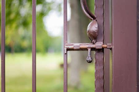 metalic texture: Rusty latch on a  brown metallic gates Stock Photo