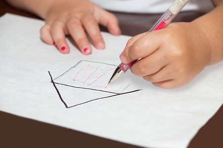 ballpen: Little girls hands with ballpen drawing a house on a white paper