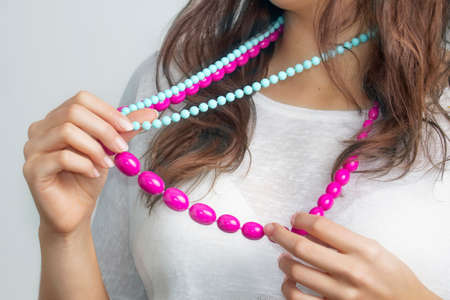avidity: Young womans holding colorful beads in her hands on a bright background
