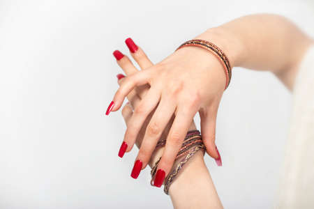Womans hands with red nails and bracelets  in a white background Stock Photo