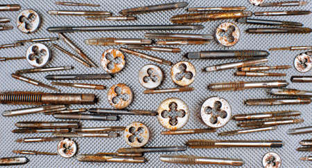 chrome base: Old rusty locksmith tools - screw taps, on grey metal background Stock Photo