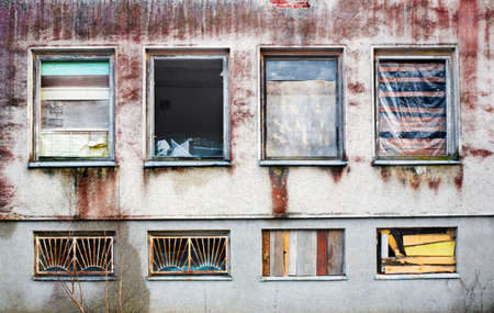Windows boarded up by wooden panels in an old house with beat all glass Stock Photo