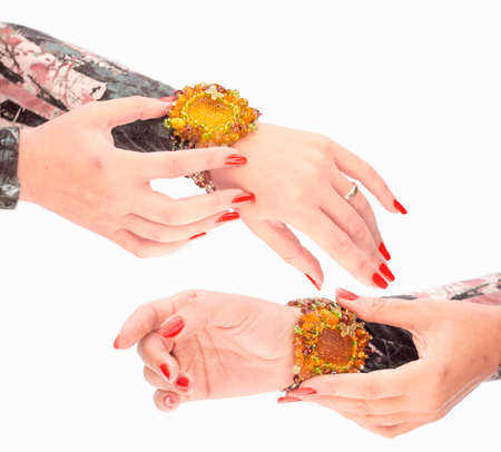 Close view of females hands with  bracelet and red nails isolated on white background