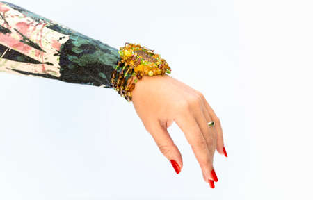 Close view of females hand with  bracelet and red nails on white background