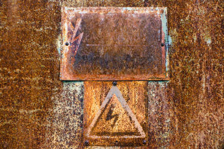 Old rusty tin surface with warning sign of high voltage for background