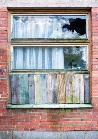 Window boarded up by wooden panels in an old red brick house with beat all glass Stock Photo