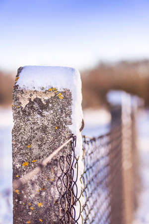 Snow on a metallic mesh fence concrete pole in winter