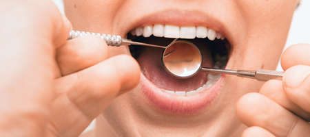 Doctor doing dental treatment to his patient in clinic. Teeth inspection and repair concept