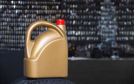 greasing: Golden plastic canister on a tire in a dark background Stock Photo