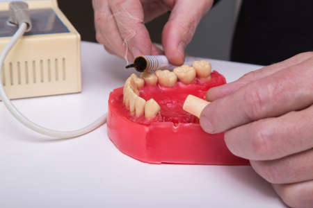 Close up of men's hands working with electric waxer on a red wax dental model on a white table