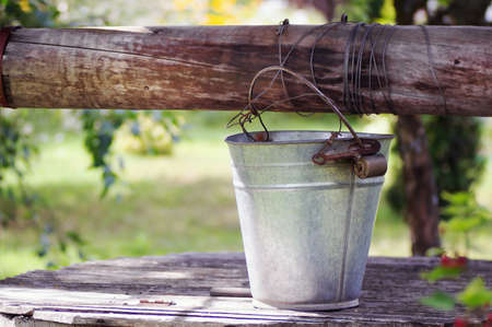 galvanized: Old galvanized bucket on a wooden well cover