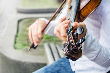 Close view of girl�s hands on a violin strings and violin scroll with pegs. Stock Photo