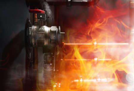 보일러 실에서 화재, 연기 및 증기. 젖은 보일러의 구리 파이프 및 밸브. 닫다 스톡 콘텐츠