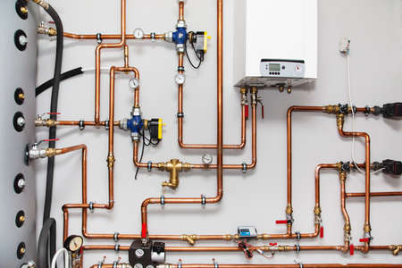 Heating system with copper pipes, valves and other equipment in a boiler room Stock Photo