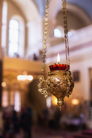 Golden candleholder with chains and flame in a church. Blured background. Close up. Stock Photo