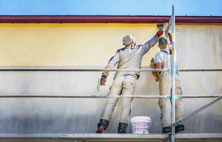 안전 비계의 두 빌더는 새 집 벽에 노란색 장식 석고를 만듭니다. 공사