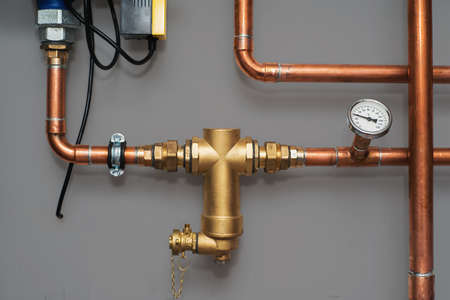 Thermometer und Wasserfilter für Zentralheizungsanlage auf einer grauen Wand in einem Heizraum. Nahansicht. Standard-Bild