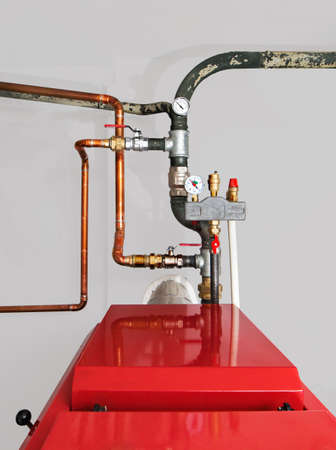 Valves, thermometer, manometer with safety valves and copper pipes on a red color boiler
