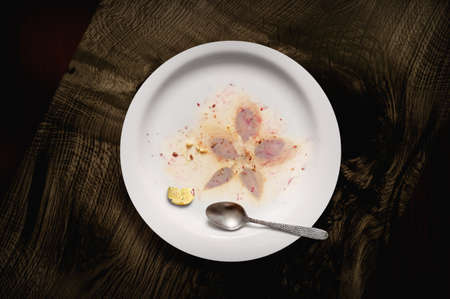 Dessert residues on a white plate with a teaspoon. Top view