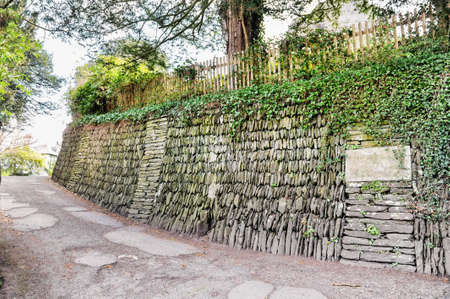 Stone based slope with wooden fance on it and the old road in UK.