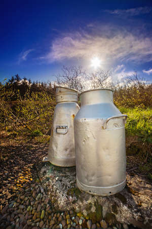 Close view of two aluminum milk cans on the roadside in a county Cork. Ireland.