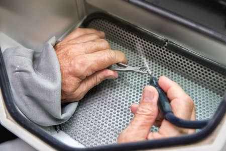 Old men hands working with with tooth prosthesis in  a dental sandblaster. Close view.