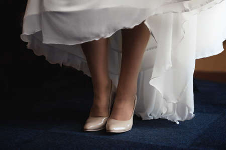 Girl's bridal gown and legs with shoes. Close view.