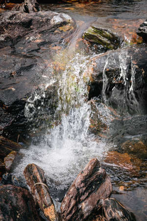 Stones in running water in a mountain river stream. Close view. Reklamní fotografie