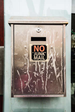Dirty postbox with the words NO JUNK MAIL. Close view.