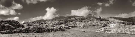 Panoramic landscape with an ancient copper mine in Allihies in spring. Ireland. Black white.