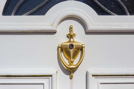 Golden door knocker with peephole on a white door with glass. Close view.