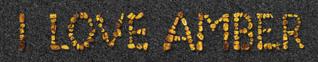 Amber pieces with inclusions placed in the text I LOVE AMBER. On a small stones gravel background. Close up. Stock Photo