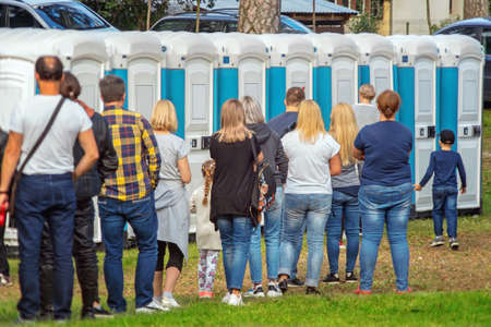 Group of people standing near portable toilets in a park