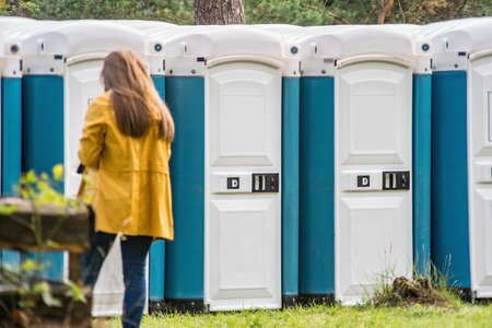 Girl going into portable toilet in a park. Stock Photo
