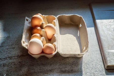 Cardboard case with big and small eggs on a table. Close up.